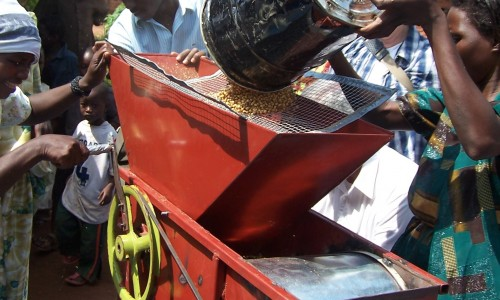 Michael Nabugere and farmers testing 2nd generation seed cleaner